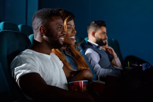 Liefde op groot scherm. knappe afrikaanse man die vrolijk lacht en zijn vriendin omhelst terwijl hij naar een film kijkt in de plaatselijke bioscoop