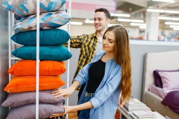 Liefde paar houdt kussens in meubelwinkel