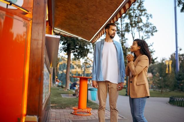 Liefde paar in de buurt van een café in pretpark, achtbaan attractie. man en vrouw ontspannen buiten. familie vrije tijd in de zomer, thema entertainment