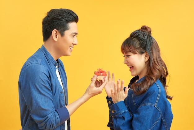 Liefde, paar, voorstel en mensenconcept - man die diamanten verlovingsring in kleine rode doos geeft aan gelukkige vrouw over gele achtergrond