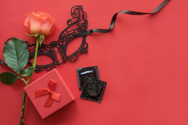 Liefde, passie, sex-romantiek plat leggen, mock-up met rode roos, kantmasker, geschenkdoos