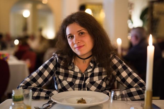 Liefde, relatie en datumconcept - gelukkige jonge vrouw bij kaarslicht tijdens romantisch diner in restaurant.