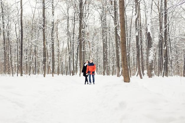 Liefde, relatie, seizoen, vriendschap en mensen concept. man en vrouw wandelen in het winterbos.