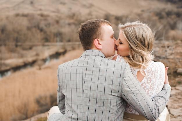 Liefde, romaans en mensenconcept - gelukkig jong paar die zitting op de rand van een klip in openlucht koesteren.
