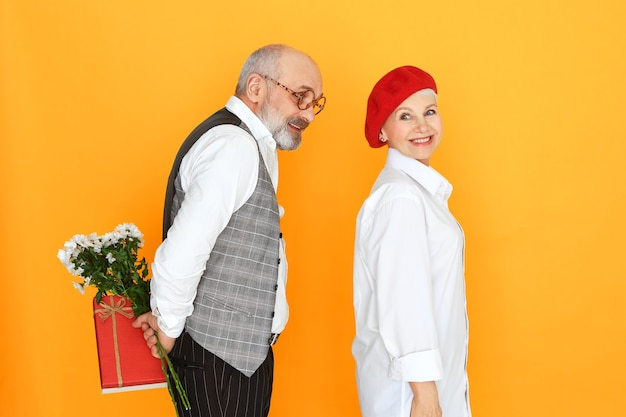 Liefde, romantiek en genegenheid concept. geïsoleerd beeld van elegante senior man met baard en kaalheid met cadeau en floers achter zijn rug, verrassing te geven aan mooie rijpe vrouw in rode baret