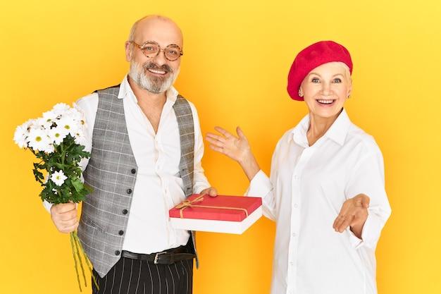 Liefde, romantiek, mensen en leeftijdsconcept. studio shot van gelukkig oudere man met kaal hoofd en dikke grijze baard flirten met aantrekkelijke stijlvolle vrouw haar bloemen en doos snoep geven op verjaardag