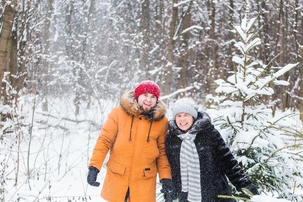 Liefde, seizoen, vriendschap en mensenconcept - gelukkige jonge man en vrouw die plezier hebben en spelen met sneeuw in het winterbos.