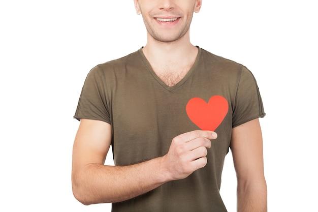 Liefde symbool. bijgesneden afbeelding van een jonge man die een papieren hart vasthoudt terwijl hij geïsoleerd op een witte achtergrond staat