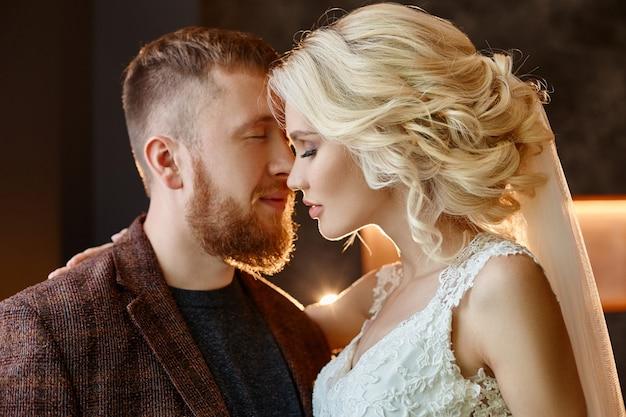 Liefde, tederheid, trouw en zorg bij elke aanraking. gelukkig stel. paar omhelsde en kuste na het huwelijk. de bruid en bruidegom omhelzen elkaar en kijken in hun ogen