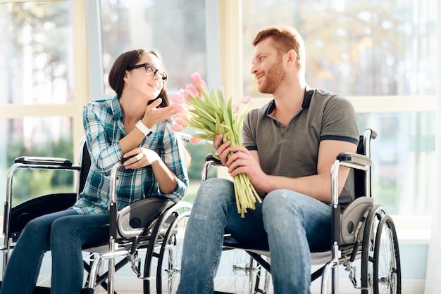 Liefde uitgeschakeld. een man en een meisje in een rolstoel zijn verliefd.