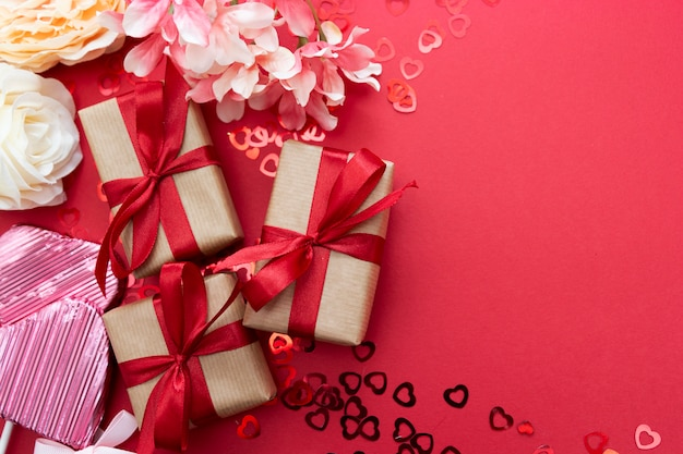 Liefde, valentijnsdag mock up, met lolly in de vorm van een hart, cadeau boxex en glitter geïsoleerd op rode achtergrond, kopie ruimte.