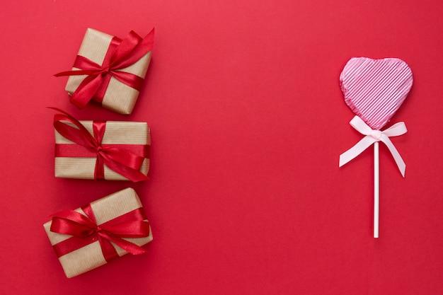 Liefde, valentijnsdagmodel omhoog, met lolly in de vorm van een hart en giftdoos, op rode achtergrond, exemplaarruimte wordt geïsoleerd die.