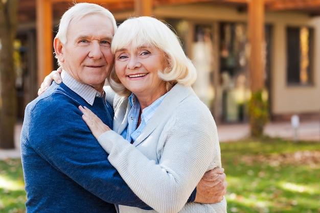 Liefde voor altijd. gelukkig senior koppel hecht zich aan elkaar en glimlacht terwijl ze buiten en voor hun huis staan