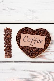 Liefde voor koffie plat gelegd. koffiebonen in de vorm van een hart en letter i.