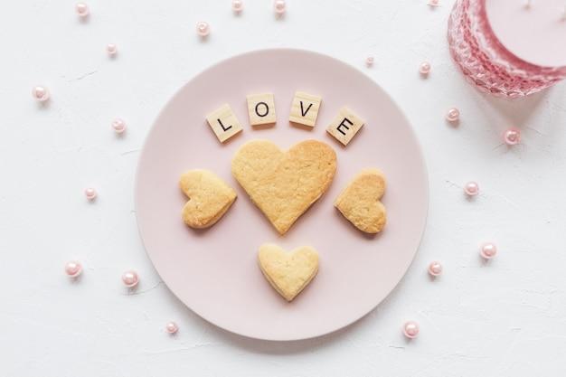Liefde woord en hartvormige koekjes op een roze plaat