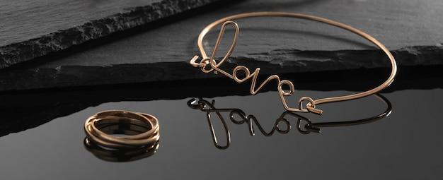 Liefde woord vorm armband en moderne ring op donkere stenen achtergrond