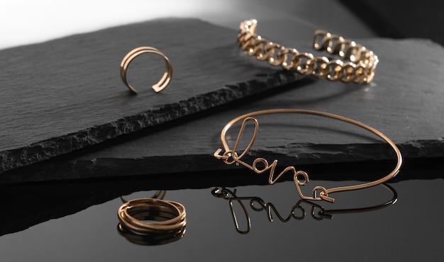 Liefde woordvorm en kettingvorm armbanden en ringen op donkere stenen platen achtergrond