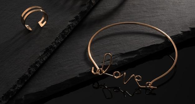 Liefde woordvorm gouden armband en gouden ring op zwarte stenen plaat op zwart oppervlak