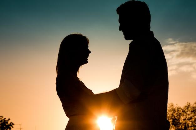 Liefde - zonsondergangpaar die elkaar omhelzen
