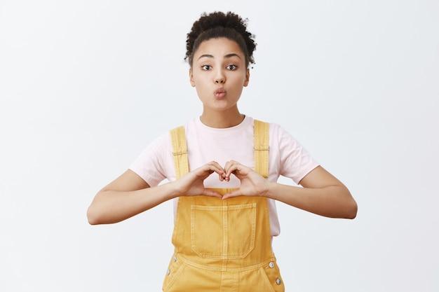 Liefde, zorg en relatie concept. portret van charmante tedere en liefdevolle afro-amerikaanse vrouw in stijlvolle gele overall, lippen vouwen in mwah en hart teken tonen over borst, kus willen
