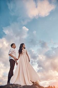 Liefdekus en omhelzingen in liefdeparen bij zonsondergang in de avond zon