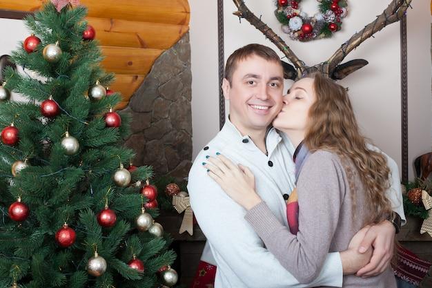 Liefdepaar dat zich dichtbij kerstboom bevindt