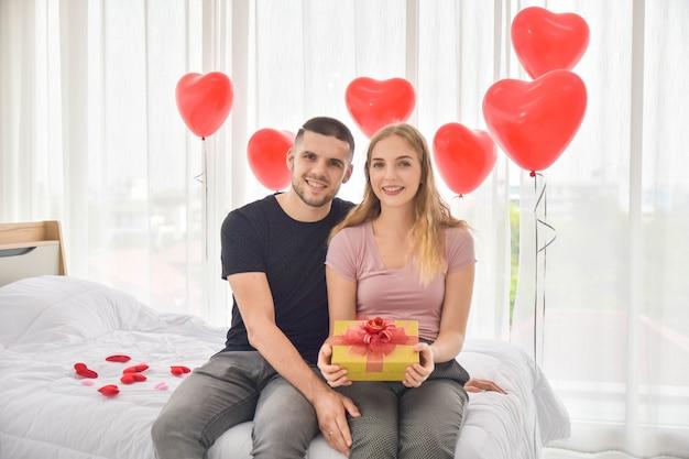 Liefdepaar die giftdoos in slaapkamergeluk geven in de dagconcept van liefdevalentine