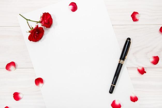 Liefdesbrief met rode roos en bloemblaadjes op witte houten tafel.