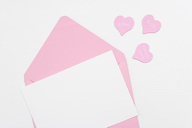 Liefdesbrief. roze envelop met witte lege kaart en harten op witte achtergrond. bovenaanzicht plat model voor uw tekst.