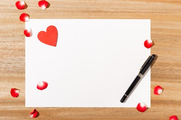 Liefdesbrief. witte kaart, rode hartvorm en pen op houten tafel. plat leggen. bovenaanzicht