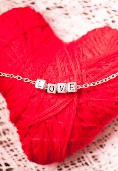 Liefdesbrieven aan de ketting close-up op rode achtergrond