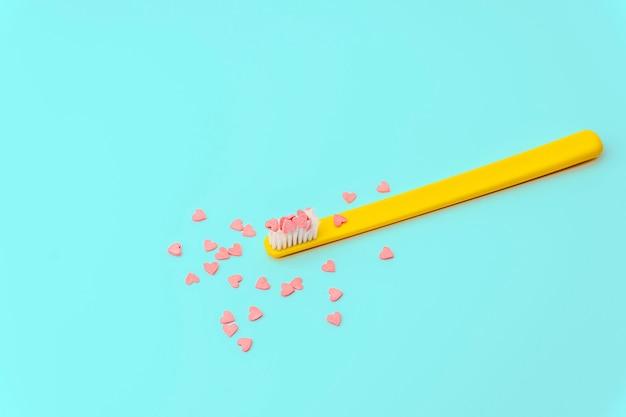 Liefdesconcept minimaal. heldere kleurrijke achtergrond met tandenborstel en suikergoedharten in roze en turkooise kleuren.