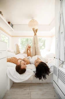 Liefdeskoppel dat ronddoolt in het bed van een camper, kampeert in een aanhangwagen. man en vrouw reizen met een busje, vakanties met de camper, kampeerders vrije tijd in de camper