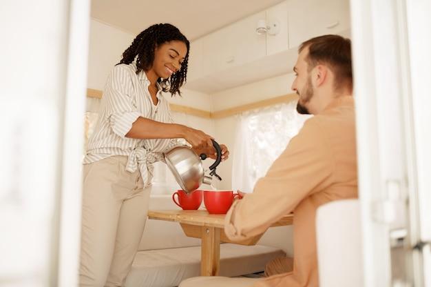 Liefdeskoppel drinkt koffie in de keuken van de camper, kamperend in een aanhangwagen. man en vrouw reizen met een busje, romantische vakanties op de camper, kampeerders maken zich vrij in de camper
