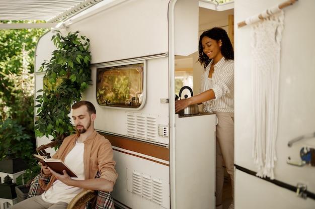 Liefdeskoppel in camper, avontuur op wielen, kamperen in een aanhangwagen. man en vrouw reizen met een busje, vakanties met de camper, kampeerders vrije tijd in de camper