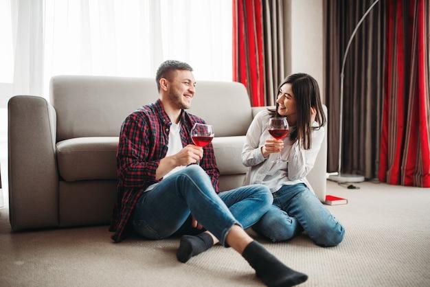 Liefdeskoppel kijkt film en drinkt rode wijn