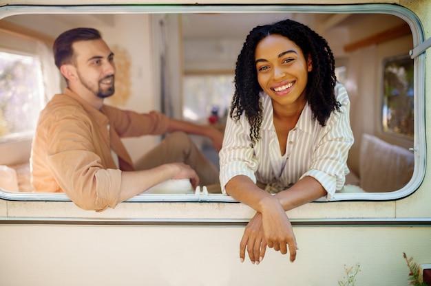 Liefdeskoppel kijkt uit het raam van de camper, kamperend in een aanhangwagen. man en vrouw reizen op busje, vakanties op camper, kampeerders vrije tijd in kampeerauto