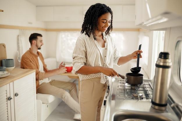 Liefdeskoppel koken in de keuken van de camper, kamperen in een aanhangwagen. man en vrouw reizen op busje, vakanties op camper, kampeerders vrije tijd in kampeerauto