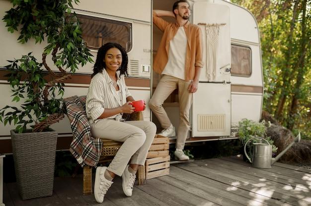 Liefdeskoppel ontspannen in camper, avontuur op wielen, kamperen in een aanhangwagen. man en vrouw reizen met een busje, vakanties met de camper, kampeerders vrije tijd in de camper