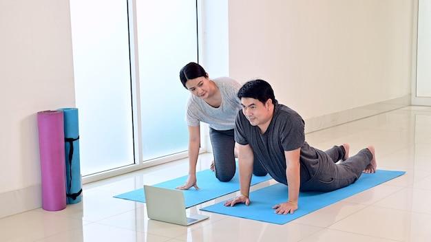 Liefdespaar online samen thuis yoga-ademhaling en meditatie leren. sport en beweging voor gezond. aziatische vrouw en man levensstijl.