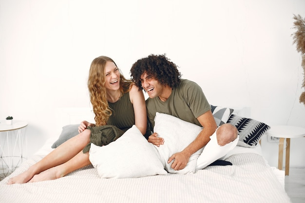 Liefdesrelatie. vrolijke paar hebben plezier op een bed. witte moderne kamer.