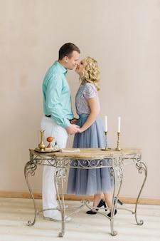 Liefdesverhaal jonge vrouw en man zijn verblijf en hand in hand. tafel met gesmede poten en kandelaar met kaarsen