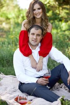 Liefdesverhaal van een liefdevol stel mannen en vrouwen in de lente in de natuur in het bos. paar knuffels, picknick in het park