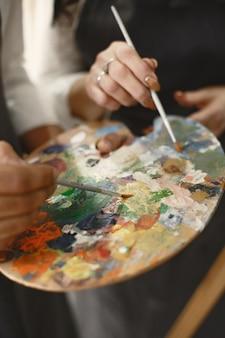 Liefdesverhaal van een volwassen stel in een kunstatelier. ze schilderen foto's, lachen, kussen elkaar. hun emoties, gevoelens, liefde.