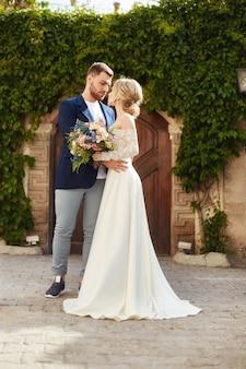 Liefdesverhaal van een vrouw en een man. verliefde paar omarmt, een mooi oosters paar. een man in een jas en een meisje in een lange luxe lichte jurk