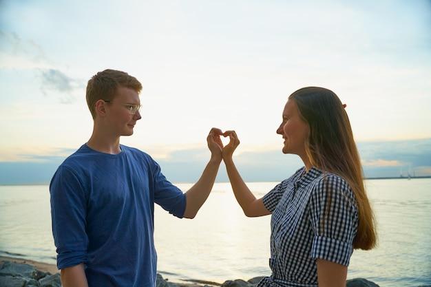 Liefdesverhaal van twee, jongen en meisje die hart met vingers maken