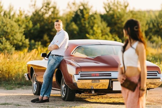 Liefdesverhaal vrouw en man met buick rivierretro stijl. unieke auto