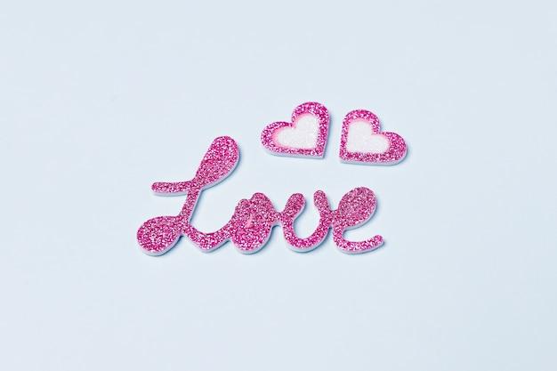Liefdeswoord in helder paars met hartjes op lichtblauwe achtergrond. valentijnsdag concept