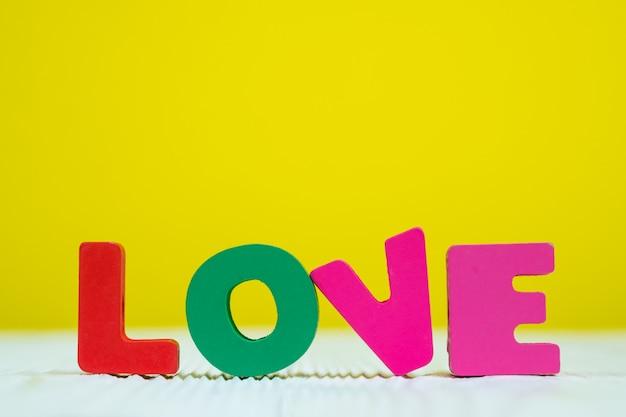 Liefdetekst op witte houten gele muurachtergrond