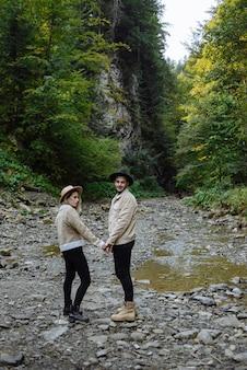 Liefdevol paar loopt langs een bergbeek terwijl ze handen opstellen. avontuur achtergrond